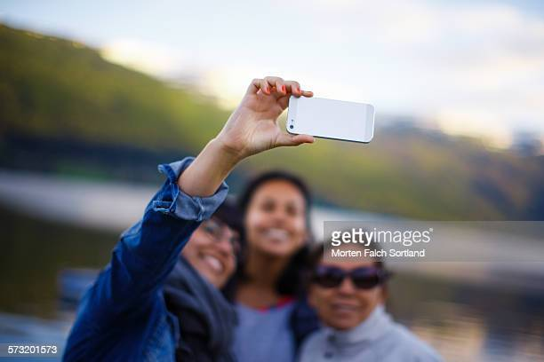 Peruvian family holding up a generic smart phone to take a family selfie in front of Vossavannet a lake in Voss Norway