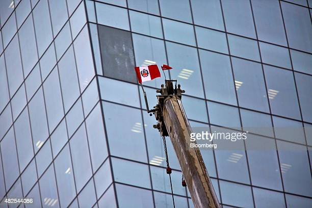 A Peruvian flag flies from a crane during construction of the Banco de la Nacion state bank headquarters building in the San Borja neighborhood of...