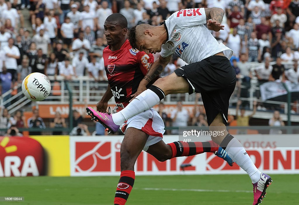Peruvian footballer Paolo Guerrero (R) of Corinthians heads the ball over Ligger of Oeste during their Paulista championship football match at Pacaembu stadium in Sao Paulo, Brazil on February 3, 2013. AFP PHOTO/Yasuyoshi CHIBA