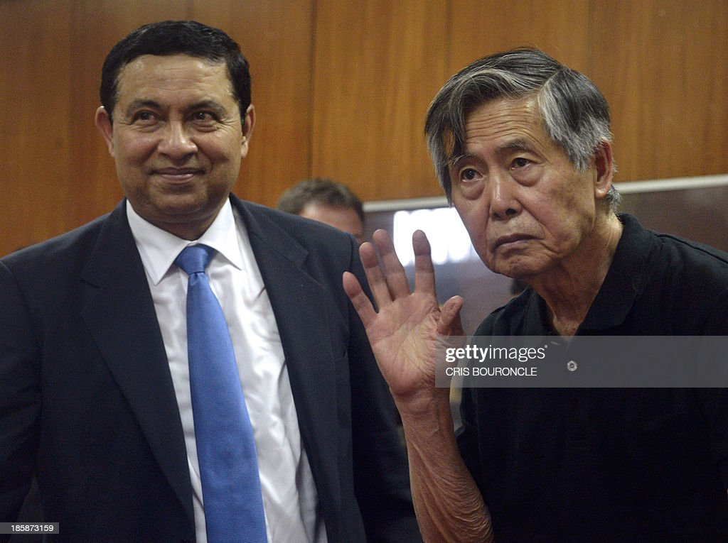 Peruvian former president (1990-2000), Alberto Fujimori (R),waves at relatives next to his lawyer William Castillo, at the end of a hearing at a facility in Ate, 16 km east of Lima, on October 25, 2013, where a judge will evaluate his request to serve out the remaining time of his 25-year sentence under house arrest. Fujimori is serving a 25-year sentence after being convicted in 2009 of human rights violations during his 1990 to 2000 presidency.