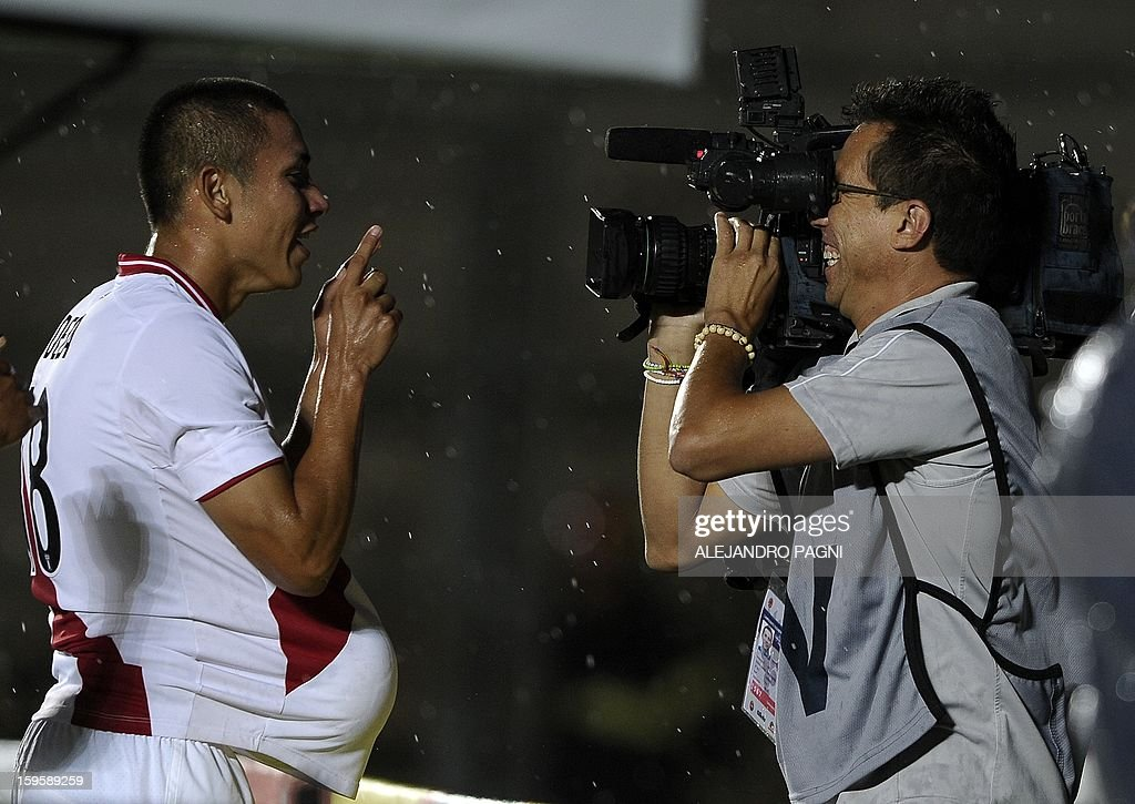 Peruvian forward Jean Deza (L) celebrates with cameraman after scoring a goal against Ecuador during the South American U-20 Championship Group B football match, at Bicentenario stadium in San Juan, Argentina, on January 16, 2013. Four South American teams will qualify for the FIFA U-20 World Cup Turkey 2013.