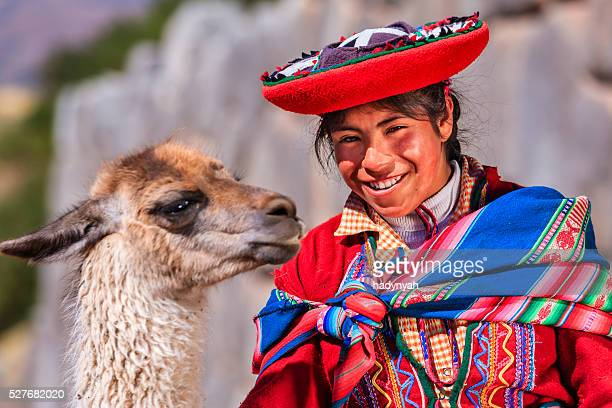Peruvian girl wearing national clothing posing with llama near Cuzco