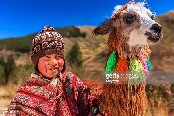 Peruanische kleine Junge trägt-Kleidung mit Lama in der Nähe liegende Cuzco