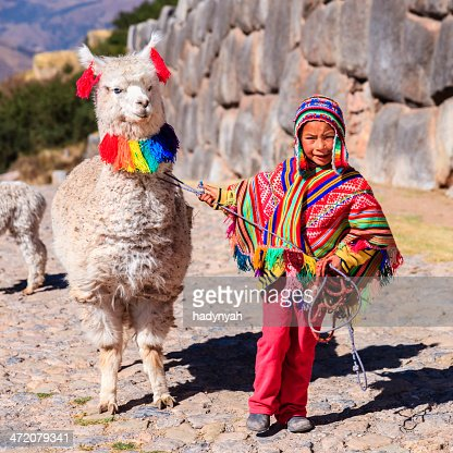 Peruvian little boy wearing national clothing with llama near Cuzco