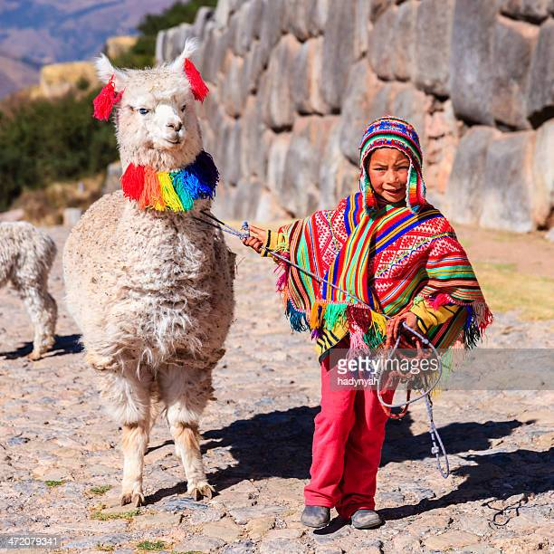 Peruvian little boy wearing national clothing with llama near Cuzco
