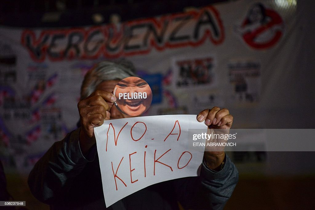A Peruvian living in Argentina holds signs reading 'Danger. No to Keiko' as he demonstrates against Peruvian presindetial candidate for the Fuerza Popular (Popular Strength) party Keiko Fujimori in Buenos Aires on May 31, 2016. Fujimori, daughter of former President (1990-2000) Alberto Fujimori, imprisoned on corruption and crimes against humanity, will face Pedro Pablo Kuczynski, of the 'Peruanos por el Kambio' (Peruvians for Change) party in next June 5 runoff elections. / AFP / EITAN