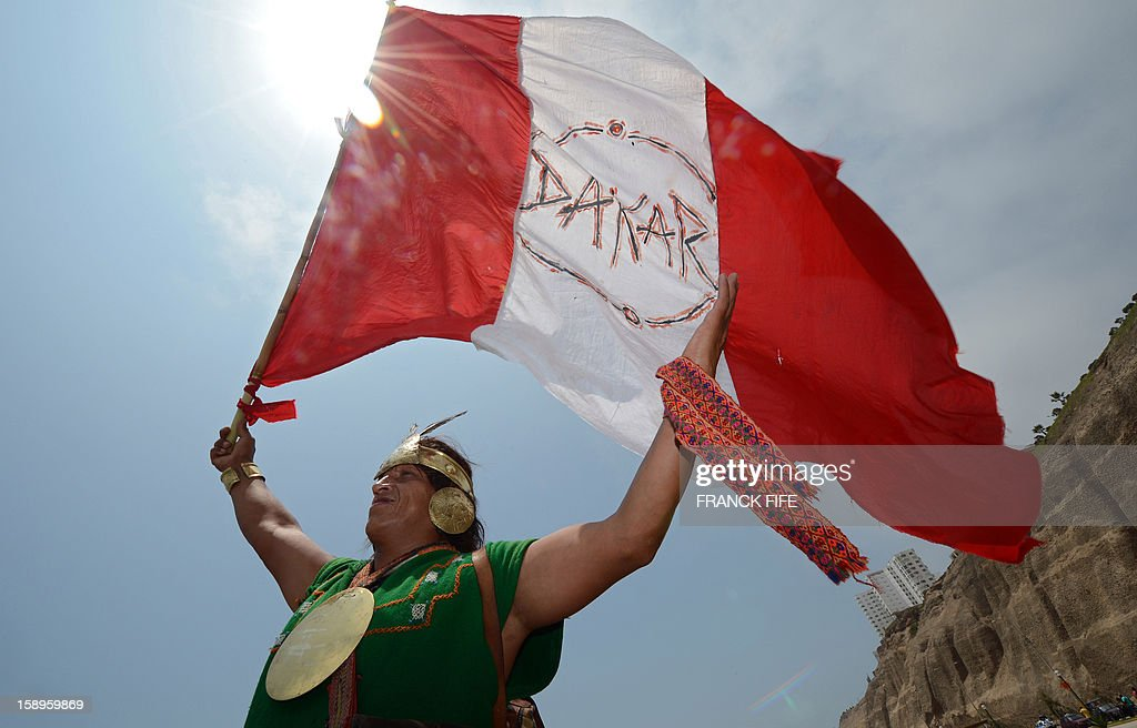 A Peruvian man dressed in ethnic costumes holds a flag of Peru reading 'Dakar' in Lima on January 4, 2013, ahead of the 2013 Dakar Rally which this year will thunder through Peru, Argentina and Chile from January 5 to 20.