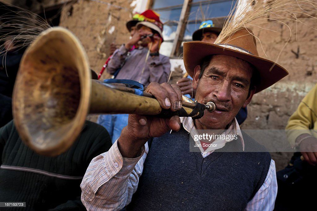A Peruvian peasant plays a trumpet during the Yawar Fiesta, a ritual fight between the condor and the bull, held in the mountains of Apurímac on 30 July 2012 in Cotabambas, Peru. The Yawar Fiesta (Feast of Blood), an indigenous tradition which dates back to the time of the conquest, consists basically of an extraordinary bullfight in which three protagonists take part - a wild condor, a wild bull and brave young men of the neighboring communities. The captured condor, a sacred bird venerated by the Indians, is tied in the back of the bull which is carefully selected for its strength and pugnacity. A condor symbolizes the native inhabitants of the Andes, while a bull symbolically represents the Spanish invaders. Young boys, chasing the fighting animals, wish to show their courage in front of the community. However, the Indians usually do not allow the animals to fight for a long time because death or harm of the condor is interpreted as a sign of misfortune to the community.