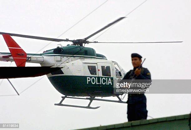 Peruvian police helicopter carrying former Peruvian spy chief Vladimiro Montesinos flies past a roof top guard enroute to an undisclosed location 25...