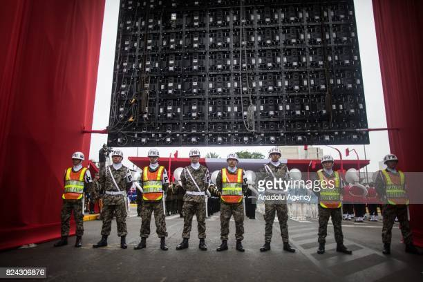 Peruvian policemen and security forces take security measures as troops perform a military parade within the celebrations for Peru's Independence Day...