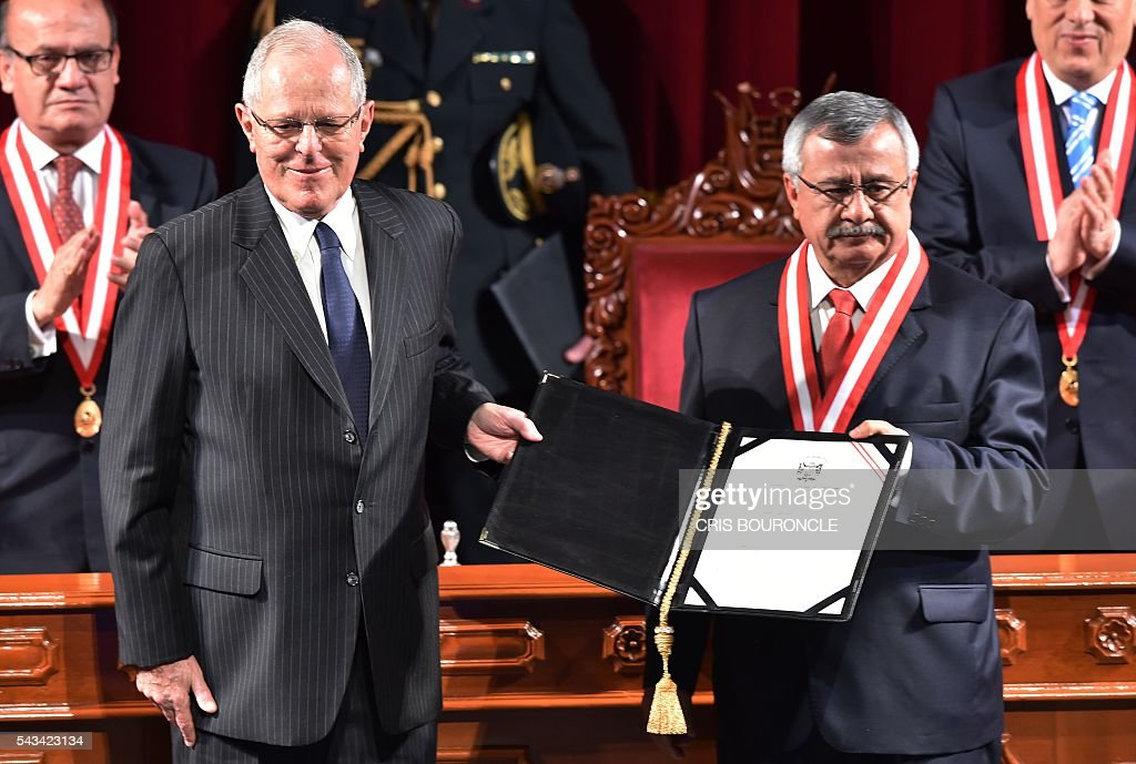 Peruvian President-elect Pedro Pablo Kuczynski (L) receives his presidential credentials from the president of the National Electoral Jury (JNE), Francisco Tavara, in Lima on June 28, 2016 a month before taking office. Kuczynski will be sworn in as president for a five-year term on July 28. / AFP / CRIS
