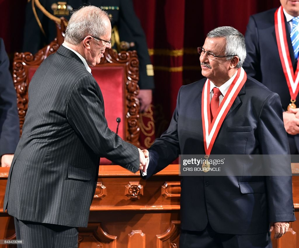 Peruvian President-elect Pedro Pablo Kuczynski (L) shakes hands with the president of the National Electoral Jury (JNE), Francisco Tavara, during the ceremony to receive his presidential credentials, in Lima on June 28, 2016 a month before taking office. Kuczynski will be sworn in as president for a five-year term on July 28. / AFP / CRIS