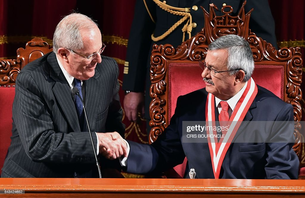 Peruvian President-elect Pedro Pablo Kuczynski (L) shakes hands with the president of the National Electoral Jury (JNE), Francisco Tavara, after receiving his presidential credentials from him in Lima on June 28, 2016 a month before taking office. Kuczynski will be sworn in as president for a five-year term on July 28. / AFP / CRIS