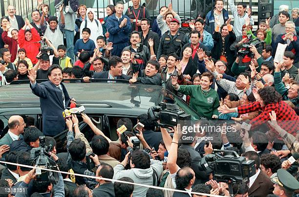 Peruvian presidential candidate Alejandro Toledo left greets supporters and the media June 3 2001 in Lima Peru as he leaves the polling station where...
