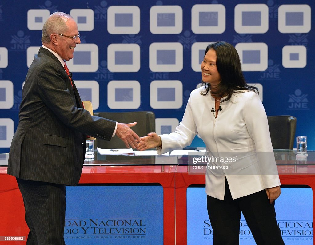 Peruvian presidential candidate for the Fuerza Popular (Popular Strength) party Keiko Fujimori (R) shakes hands with Peruvian presidential candidate Pedro Pablo Kuczynski of the 'Peruanos por el Kambio' (Peruvians for change) party before a televised debate in Lima on May 29, 2016. Fujimori and Kuczynski will compete in Peru's June 5 runoff election. / AFP / CRIS