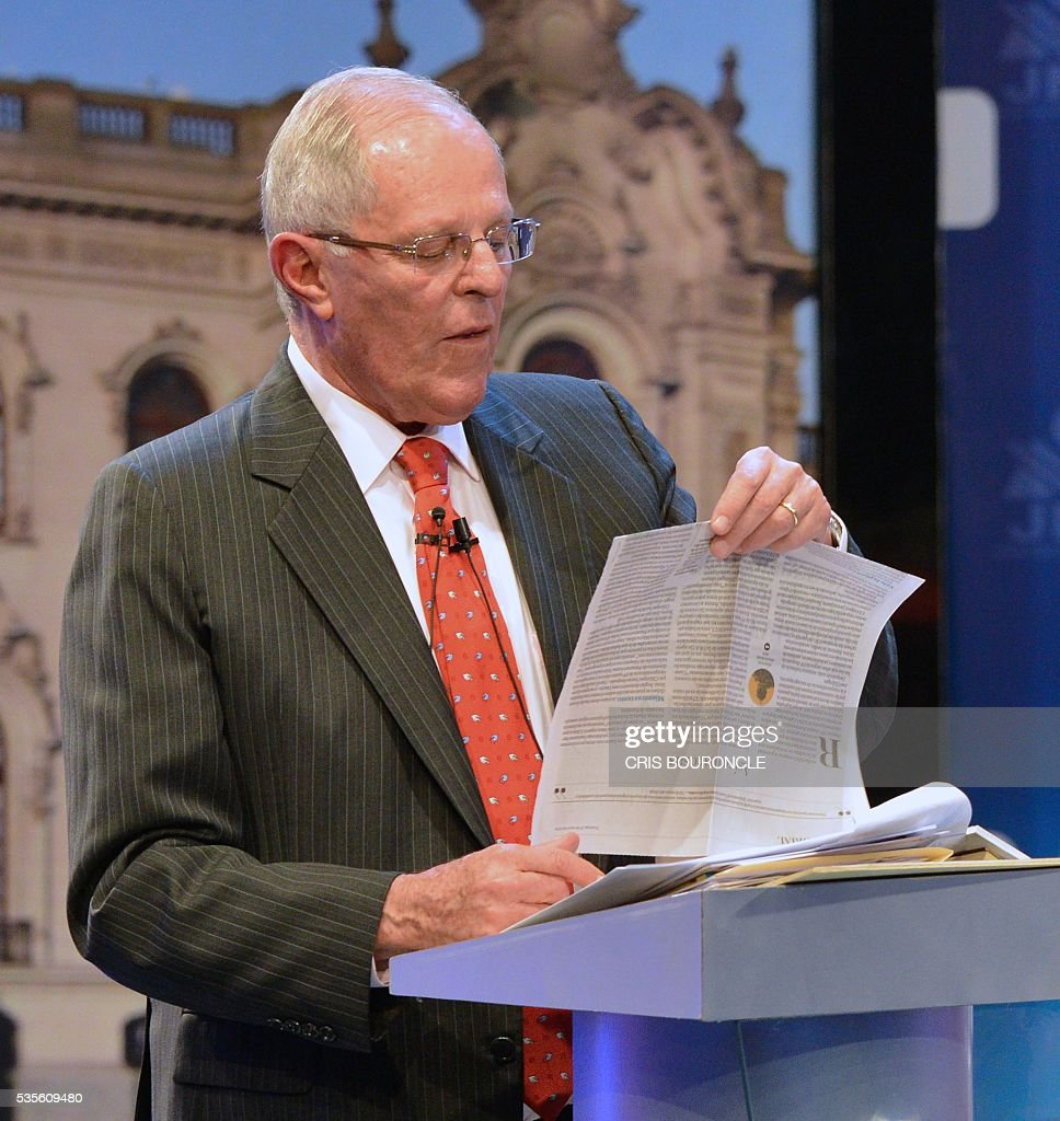 Peruvian presidential candidate Pedro Pablo Kuczynski of the 'Peruanos por el Kambio' (Peruvians for change) party reads from a newspapaer article during a televised debate with Peruvian presidential candidate for the Fuerza Popular (Popular Strength) party Keiko Fujimori (out of frame) in Lima on May 29, 2016. Fujimori and Kuczynski will compete in Peru's June 5 runoff election. / AFP / CRIS