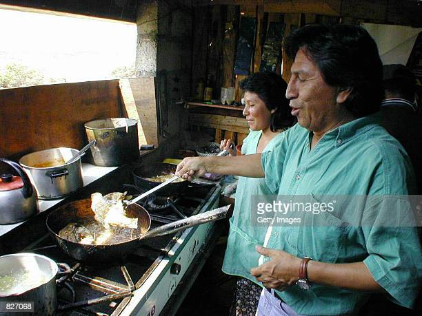 Peruvian Presidential frontrunner Alejandro Toledo right helps a housewife cook a meal in Chepen a small town north of Lima March 2 2001 during his...