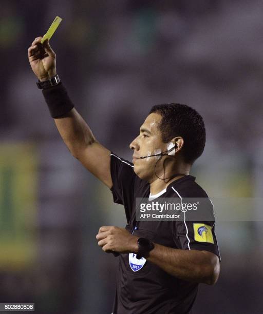 Peruvian referee Diego Haro shows a yellow card to Brazil's Chapecoense midfielder Andrei Girotto during the Copa Sudamericana second round first leg...