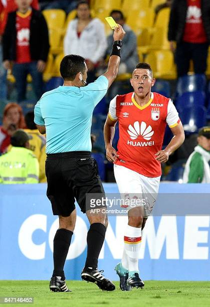 Peruvian referee Diego Haro shows the yellow card to Colombia's Santa Fe Daniel Buitrago during their Copa Sudamericana football match against...