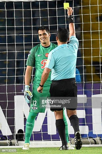 Peruvian referee Diego Haro shows the yellow card to Paraguay's Libertad goalie Carlos Servin during their Copa Sudamericana football match against...