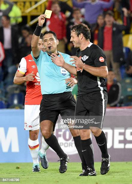 Peruvian referee Diego Haro shows the yellow card to Paraguay's Libertad Adalberto Roman during their Copa Sudamericana football match against...