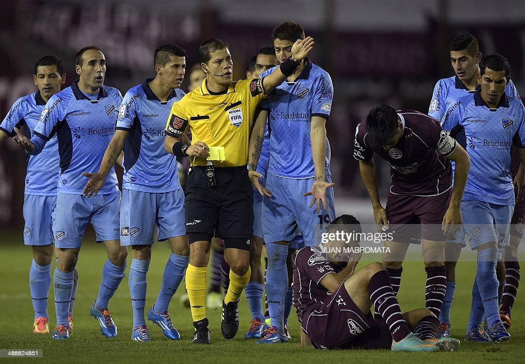Peruvian referee Victor Carrillo (C) gestures during the Libertadores Cup quarterfinal first leg football match between Argentina's team Lanus and Bolivia's Bolivar, in Lanus, Buenos Aires, on May 8, 2014. AFP PHOTO / Juan Mabromata