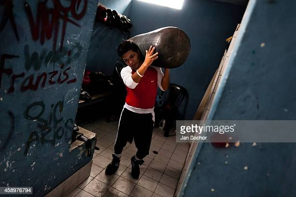 Peruvian teen carries a punching bag from the changing room at VMT Boxing Club on July 3 2013 in Lima Peru Boxeo VMT is a grassroots organisation...
