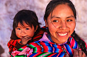 Peruvian woman carrying her baby on back