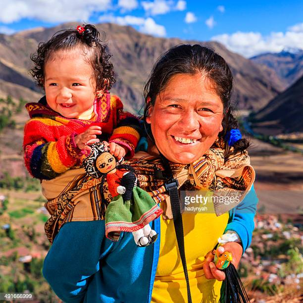 Peruvian woman with her baby on the back near Pisac