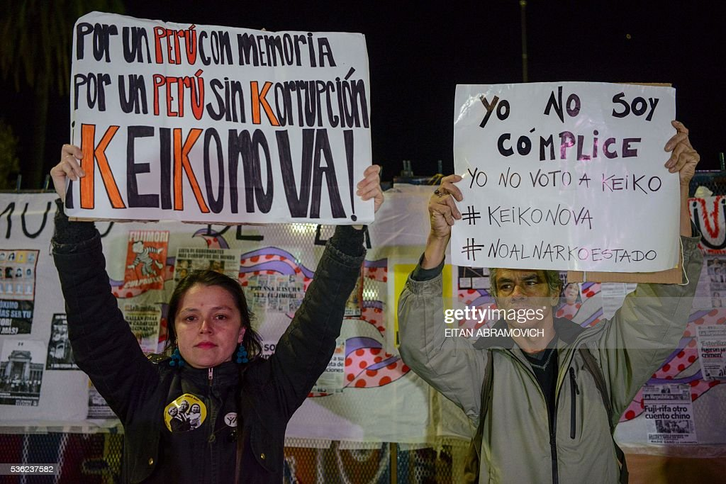 Peruvians living in Argentina hold signs against Peruvian presidential candidate for the Fuerza Popular (Popular Strength) party Keiko Fujimori in Buenos Aires on May 31, 2016. Fujimori, daughter of former President (1990-2000) Alberto Fujimori, imprisoned on corruption and crimes against humanity, will face Pedro Pablo Kuczynski, of the 'Peruanos por el Kambio' (Peruvians for Change) party in next June 5 runoff elections. / AFP / EITAN