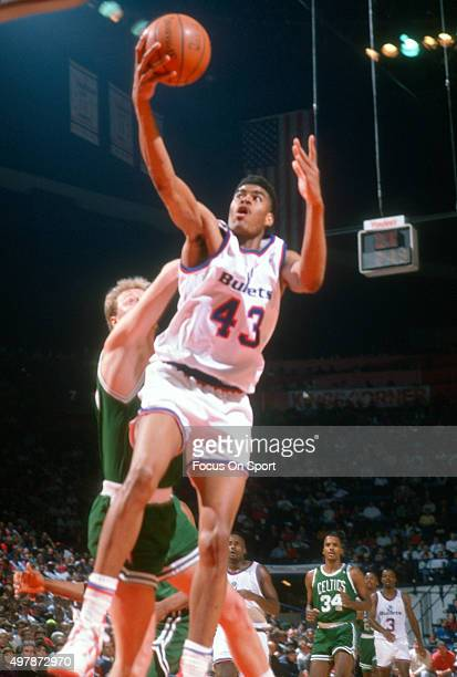 Pervis Ellison of the Washington Bullets grabs a rebound over Larry Bird of the Boston Celtics during an NBA basketball game circa 1991 at the...