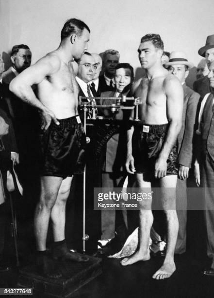 Pesée du boxeur Jack Sharkey sous l'oeil attentif de son futur adversaire Max Schmeling le 21 juin 1932 à New York EtatsUnis