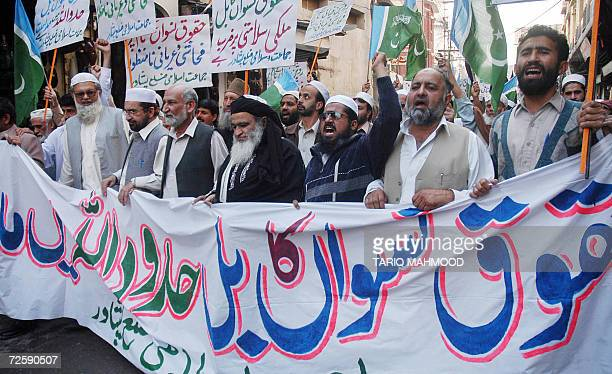 Pakistani activists of the fundamentalist Islamic alliance of Muttahida MajliseAmal carry placards and banners as they march during a protest in...