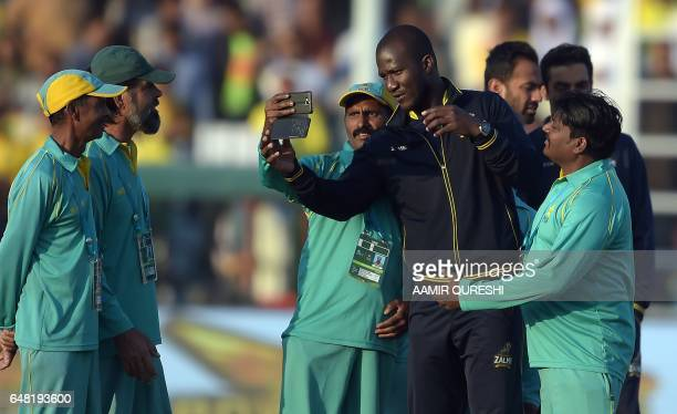 Peshawar Zalmi captain West Indies Darren Sammy takes a 'selfie' with Pakistani groundstaff members prior to the start of the final cricket match of...