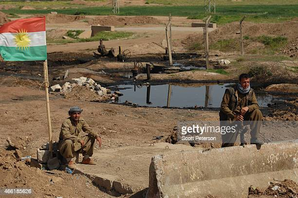 A peshmerga checkpoint stands beside pools of oil with damaged oil pipeline infrastructure as Iraqi Kurdish forces push the frontline forward against...