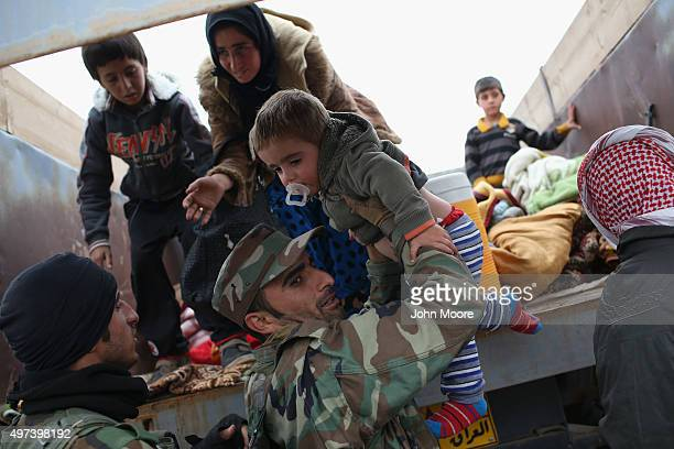 Peshmerga fighter assists families fleeing their frontline village to a Kurdishcontrolled area on November 16 2015 near Sinjar Iraq Peshmerga forces...