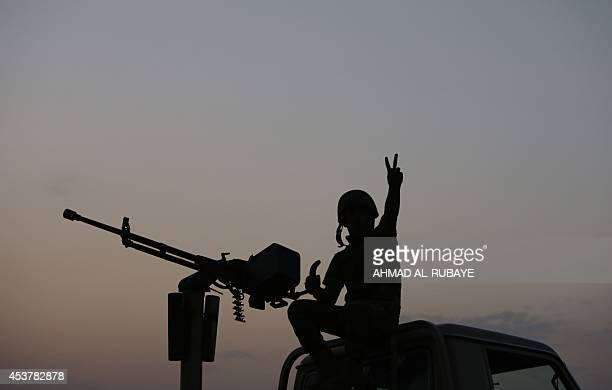 A Peshmerga fighter flashes the sign for victory on top of an armoured vehicle on the front line of fighting with Islamic State militants 20...