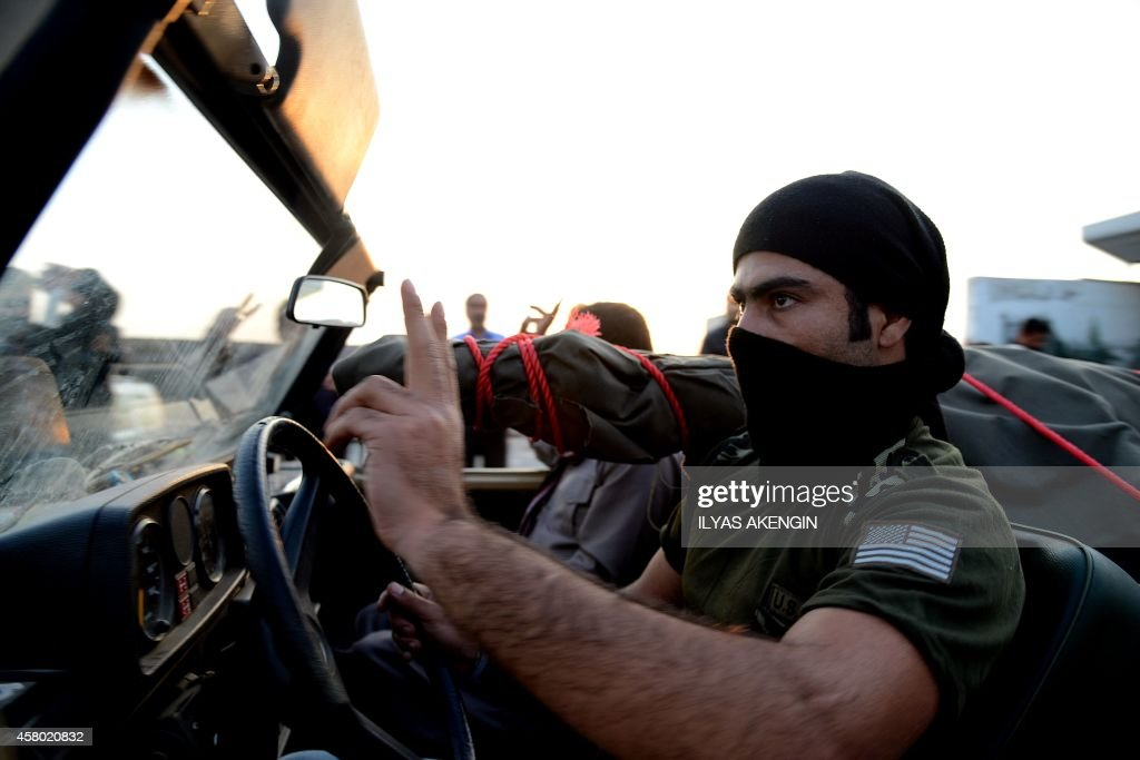 A peshmerga fighter flashes victory sign as their convoy arrives at the Habur crossing along the TurkishIraqi border with heavy weapons on October 29...