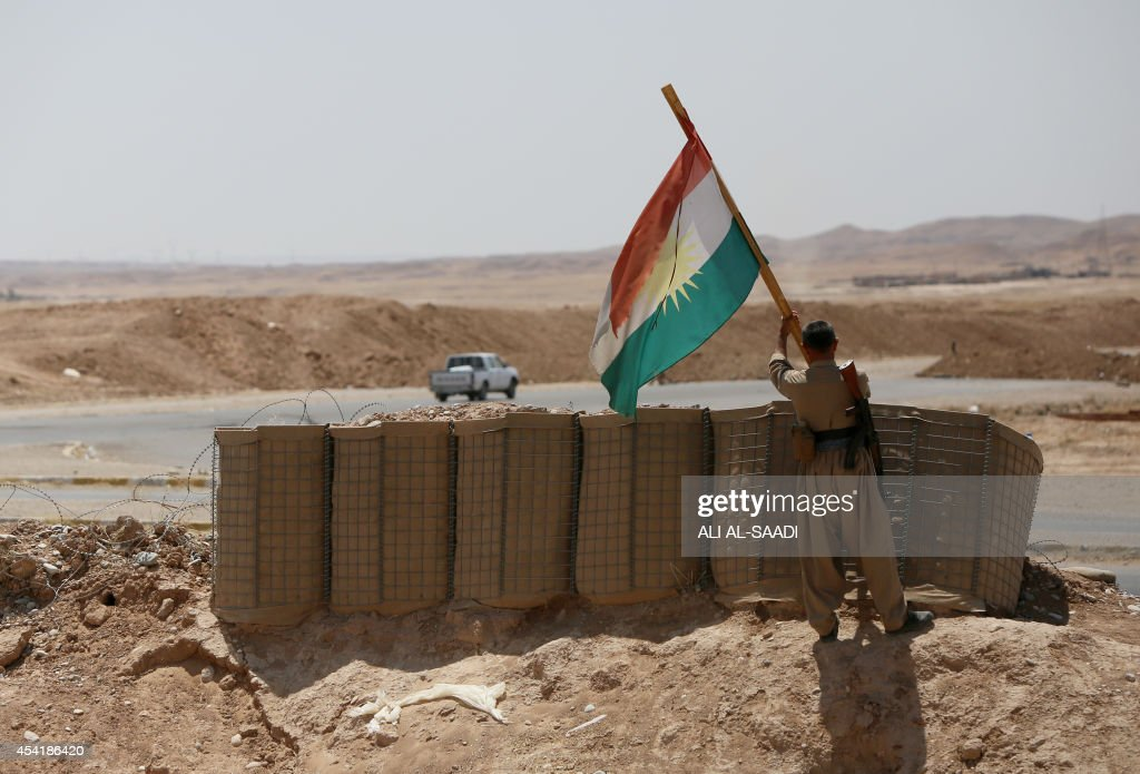 A peshmerga fighter puts up a Kurdish flag at a position near the strategic Jalawla area, in Diyala province, which is a gateway to Baghdad, as battles with Islamic State (IS) jihadists continue on August 25, 2014. Kurdish forces backed by Iraqi air support retook three villages in the Jalawla area, as well as a main road used by jihadists to transport fighters and supplies, peshmerga members said.