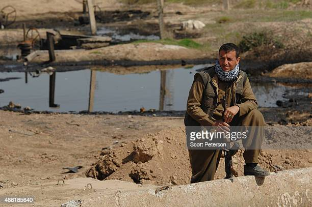 A peshmerga fighter stands guard beside pools of oil with damaged oil pipeline infrastructure as Iraqi Kurdish forces push the frontline forward...