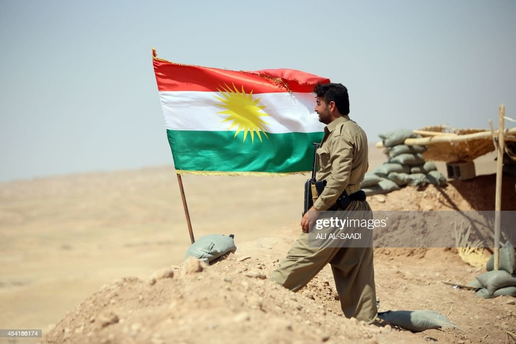 A peshmerga fighter stands next to a Kurdish flag as he guards a position near the strategic Jalawla area, in Diyala province, which is a gateway to Baghdad, as battles with Islamic State (IS) jihadists continue on August 25, 2014. Kurdish forces backed by Iraqi air support retook three villages in the Jalawla area, as well as a main road used by jihadists to transport fighters and supplies, peshmerga members said.