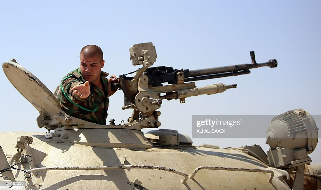A Peshmerga fighters gestures from an armed military vehicle as he guards a post in the strategic Jalawla area, in Diyala province, which is a gateway to Baghdad, as battles with Islamic State (IS) jihadists continue on August 25, 2014. Kurdish forces backed by Iraqi air support retook three villages in the Jalawla area, as well as a main road used by jihadists to transport fighters and supplies, peshmerga members said.