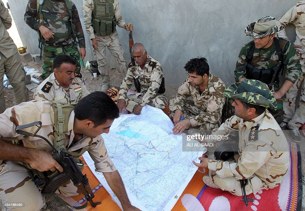 Peshmerga fighters look at a map as they hold a position near the strategic Jalawla area, in Diyala province, which is a gateway to Baghdad, as battles with Islamic State (IS) jihadists continue on August 25, 2014. Kurdish forces backed by Iraqi air support retook three villages in the Jalawla area, as well as a main road used by jihadists to transport fighters and supplies, peshmerga members said.