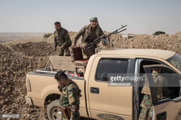 Peshmerga fighters prepare equipment as they fortify positions on the frontline outside the town of Altun Kubri on October 23 2017 in Altun Kubri...