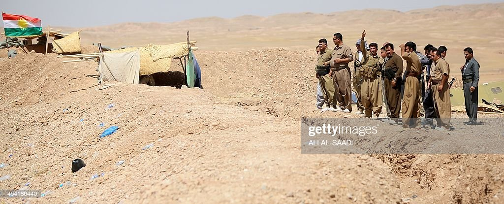 Peshmerga fighters stand next to trench as they hold a position near the strategic Jalawla area, in Diyala province, which is a gateway to Baghdad, as battles with Islamic State (IS) jihadists continue on August 25, 2014. Kurdish forces backed by Iraqi air support retook three villages in the Jalawla area, as well as a main road used by jihadists to transport fighters and supplies, peshmerga members said.