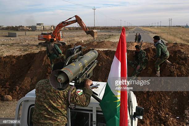 Peshmerga soldier aims a Milan antitank missile towards an ISIL position as a bulldozer builds berms and trenches on the new frontline on November 15...