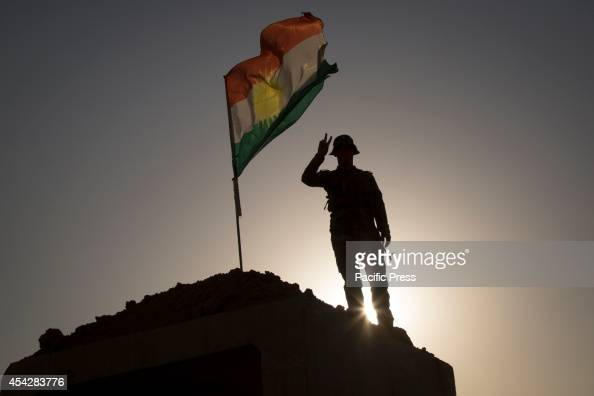 Peshmerga soldier makes a victory sign on top of a bunker at the Khazir Frontline Khazir refugee camp is located outside Kalak a town halfway on the...