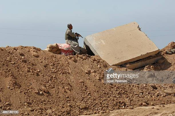 A peshmerga soldier mans a position atop a dirt berm as Iraqi Kurdish forces push the frontline forward against ISIS forces in the Tal alWard...