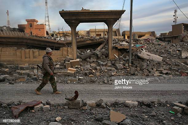 Peshmerga soldier walks past the rubble of a neighborhood on November 15 2015 in Sinjar Iraq Kurdish forces with the aid of massive USled coalition...
