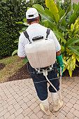 Pest control technician with portable spray rig using spray hose